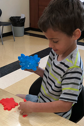 A student interacting with Play-Doh in a student activity at our Summer Program.