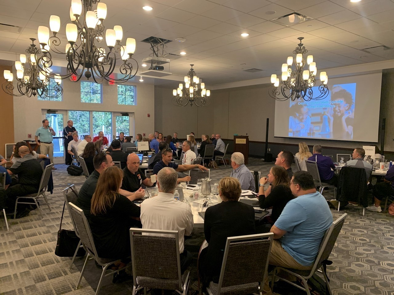 TCESC Superintendent Michael Hanshaw, standing at right, welcomes s Trumbull County Administrators to the TCESC-hosted 2021 Conference. Bristol Superintendent Chris Dray, standing at left, introduces his administrators.
